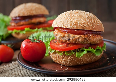 Sandwich with chicken burger, tomatoes and lettuce - stock photo