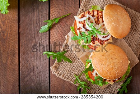 Sandwich with chicken burger, tomatoes, cheese and lettuce. Top view - stock photo