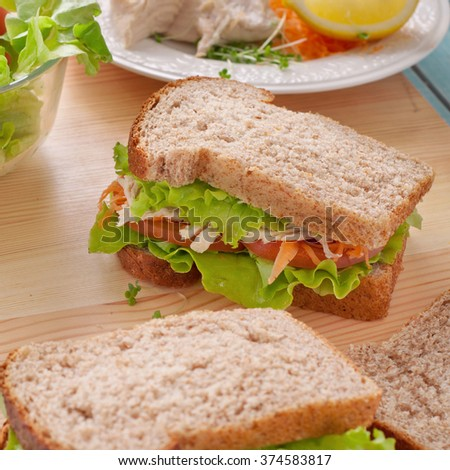 Sandwich with chicken on a wooden board in the kitchen. Top view with space for object. square frame