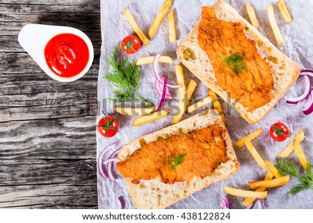 sandwich with ciabatta and bread crumb coated fried pork chop with french fries, red onion, cherry tomatoes and dill on a parchment paper, view from above  - stock photo