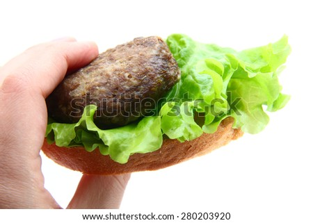 sandwich with cutlet and leaf lettuce in hand on white background - stock photo