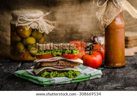 Sandwich with fresh smoked meat, cheese, lettuce and tomato with homemade ketchup - stock photo
