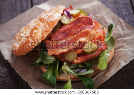 Sandwich with fried bacon, tomato and pickles