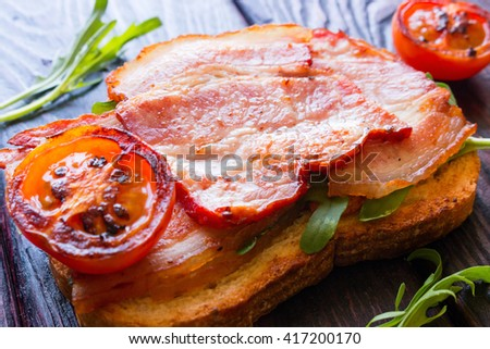 sandwich with fried bacon, tomatoes and arugula - stock photo