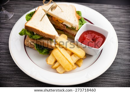 Sandwich with fried eggs, bacon and lettuce served with french fries and ketchup - stock photo
