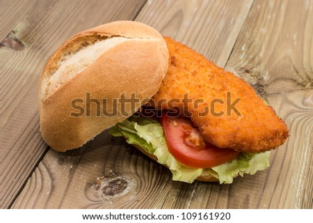 Sandwich with fried meat on wooden background - stock photo