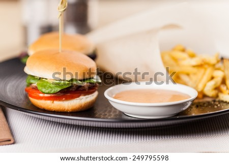 Sandwich with golden french fries potatoes. tray with burger and fries on table - stock photo