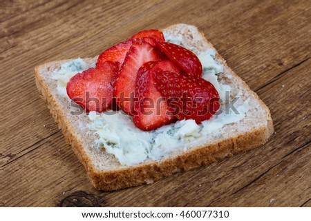 Sandwich with gorgonzola and strawberry on the wood background