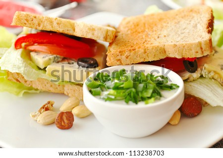Sandwich with green salad, nuts, roasted bread, cheese in a cafe