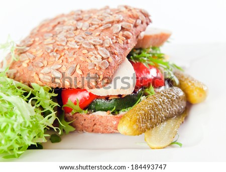 sandwich with grilled vegetables and chicken on white plate