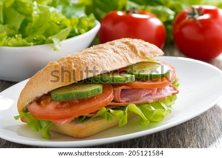 sandwich with ham and fresh vegetables on a plate, close-up - stock photo