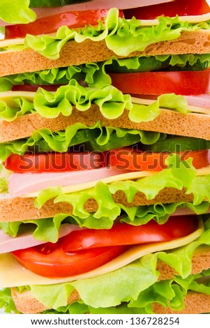 Sandwich with ham,cheese and fresh vegetables isolated on white background - stock photo