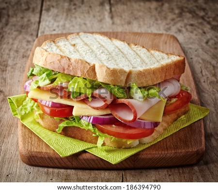 Sandwich with ham, cheese and fresh vegetables on wooden cutting board - stock photo