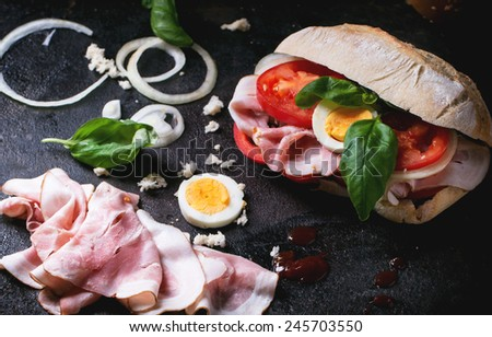 Sandwich with ham, eggs, vegetables and ketchup, served with french fries over black background. See series - stock photo