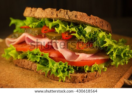 Sandwich with ham, fresh lettuce, tomatoes, salty cucumber and chili pepper on a cork board and wooden background
