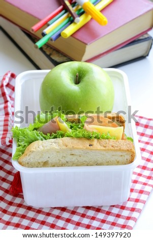 sandwich with ham, green salad and apple in a box - school lunch - stock photo