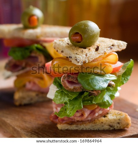 Sandwich with ham, sausage, cheese, tomato and lettuce, selective focus - stock photo