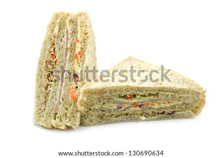 sandwich with ham, tuna and vegetables on white background