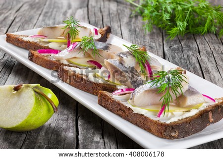 sandwich with herring fillets, onion, green sliced apple, creamy cheese and dill on a rectangular dish on an old rustic table, close-up  - stock photo