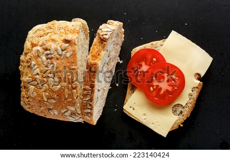 Sandwich with homemade bread with cheese and tomato on a black background - stock photo