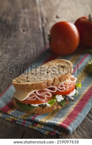 Sandwich with lettuce, tomato, ham and cheese - stock photo