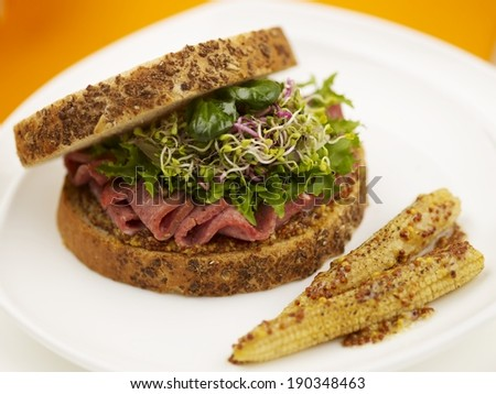 Sandwich with lunch meat and sprouts served on plate
