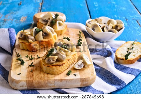 Sandwich with mushrooms and thyme on a wooden surface - stock photo