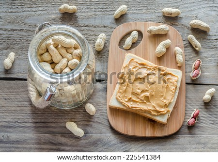 Sandwich with peanut butter on the wooden board - stock photo