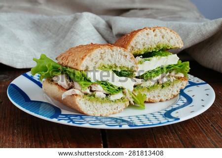 Sandwich with pesto, chicken and mozzarella cheese - stock photo