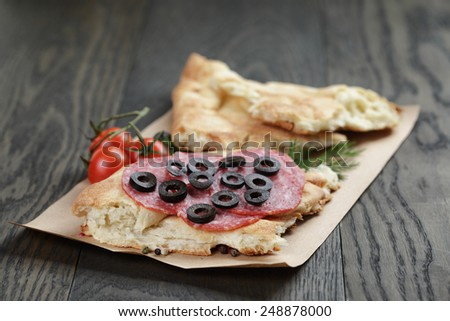 sandwich with pita bread salami and vegetables on wood table - stock photo