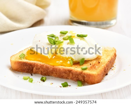 Sandwich with poached egg and green onion on white plate - stock photo