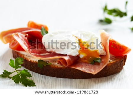 Sandwich with poached egg, parma ham and cream cheese - stock photo