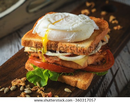 Sandwich with poached egg, tomato, bacon and green salad on a wooden vintage background in rustic style. Toned.