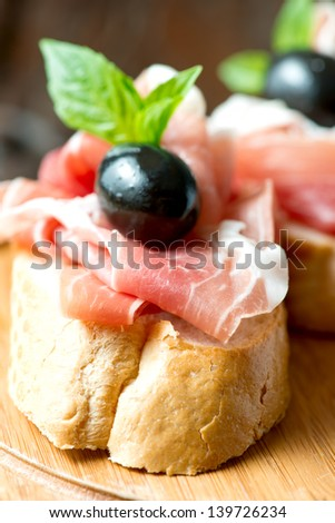 Sandwich with prosciutto, olive on wooden cutting board - stock photo