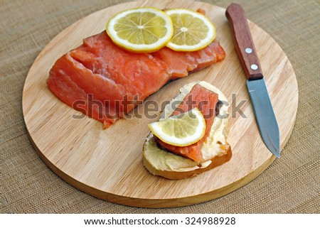 Sandwich with red fish and slice of lemon, close-up - stock photo