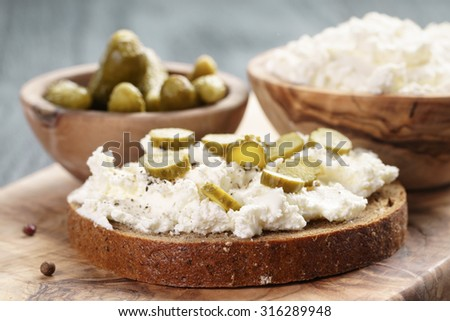 sandwich with rye bread, cream cheese and marinated cucumbers, rustic food - stock photo