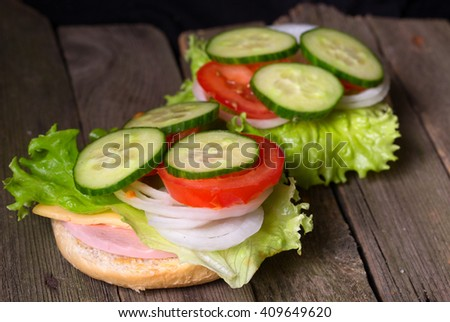 Sandwich with salad and other vegetables on old gray boards. On a half of a roll the lettuce leaf, onions rings, a tomato piece, sausage lies. Close up, small depth of sharpness - stock photo