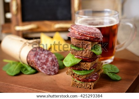 Sandwich with Salami and Spinach on Rustic Wooden Table, Lager Beer in the Background.  - stock photo