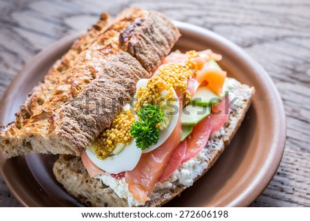 Sandwich with salmon, avocado and eggs - stock photo