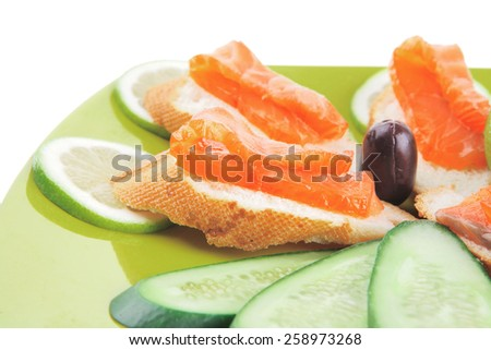 sandwich with salmon on green over white - stock photo