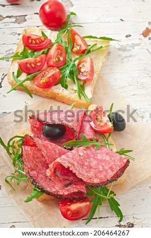 Sandwich with sausage, olive, tomato and arugula on the old wooden background