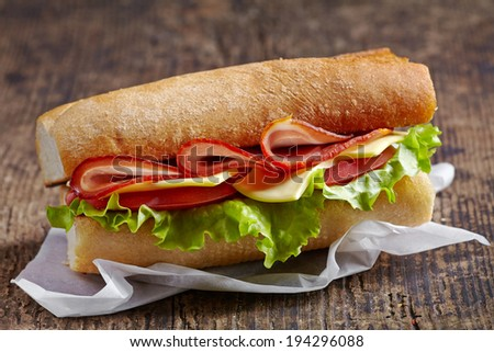 Sandwich with serrano ham and vegetables on wooden table - stock photo