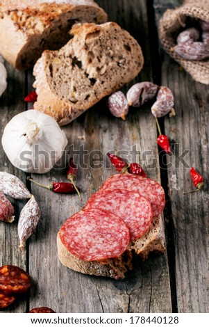 Sandwich with sliced salami served with other sausages, fresh bread, garlic and red hot chili peppers on old wooden table. See series - stock photo