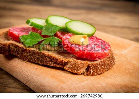 sandwich with sliced sausage and cucumber on wooden cutting board - stock photo
