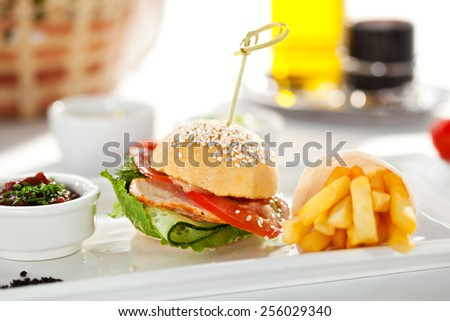 Sandwich with Smoked Meat, Tomato and Cucumber. Garnished with French Fries and Vegetables Sauce - stock photo