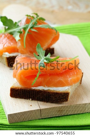 Sandwich with smoked salmon and arugula on a wooden board - stock photo