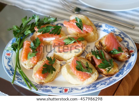 Sandwich with smoked salmon and parsley on a plate on the dinner table. Elegant canape with salmon/Sandwich with red fish. salmon canape on buffet table - stock photo