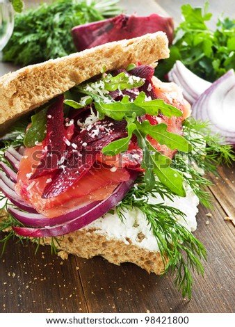 Sandwich with smoked salmon, cottage cheese and herbs. Shallow dof. - stock photo