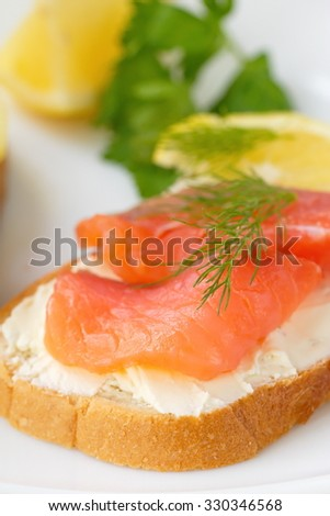 Sandwich with smoked salmon, cream cheese and lemon on plate