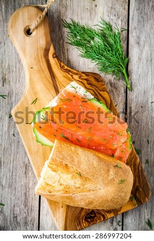 sandwich with smoked salmon, cream cheese, cucumber and dill on wooden table - stock photo